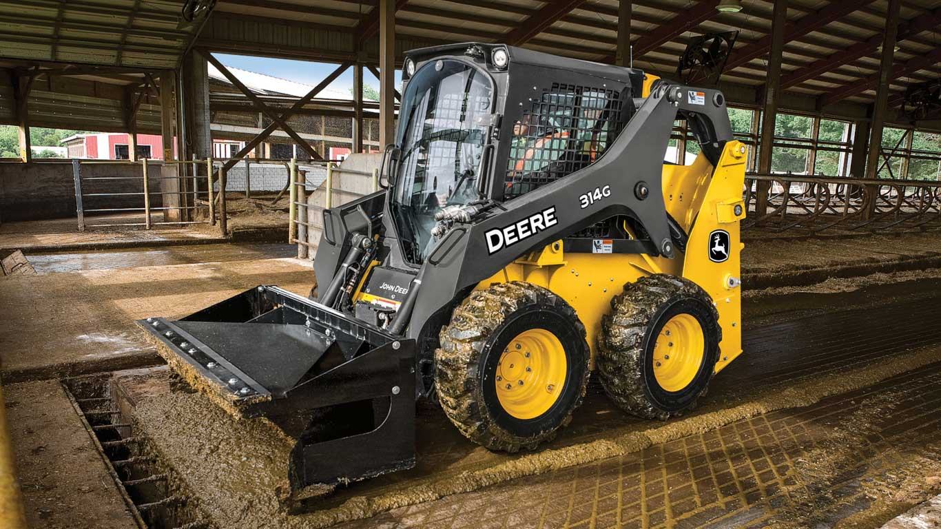 314G Skid Steer with material scraper working in a livestock confinement
