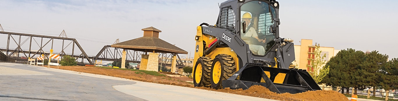 skid steer with a landplane attachment on a jobsite in a park