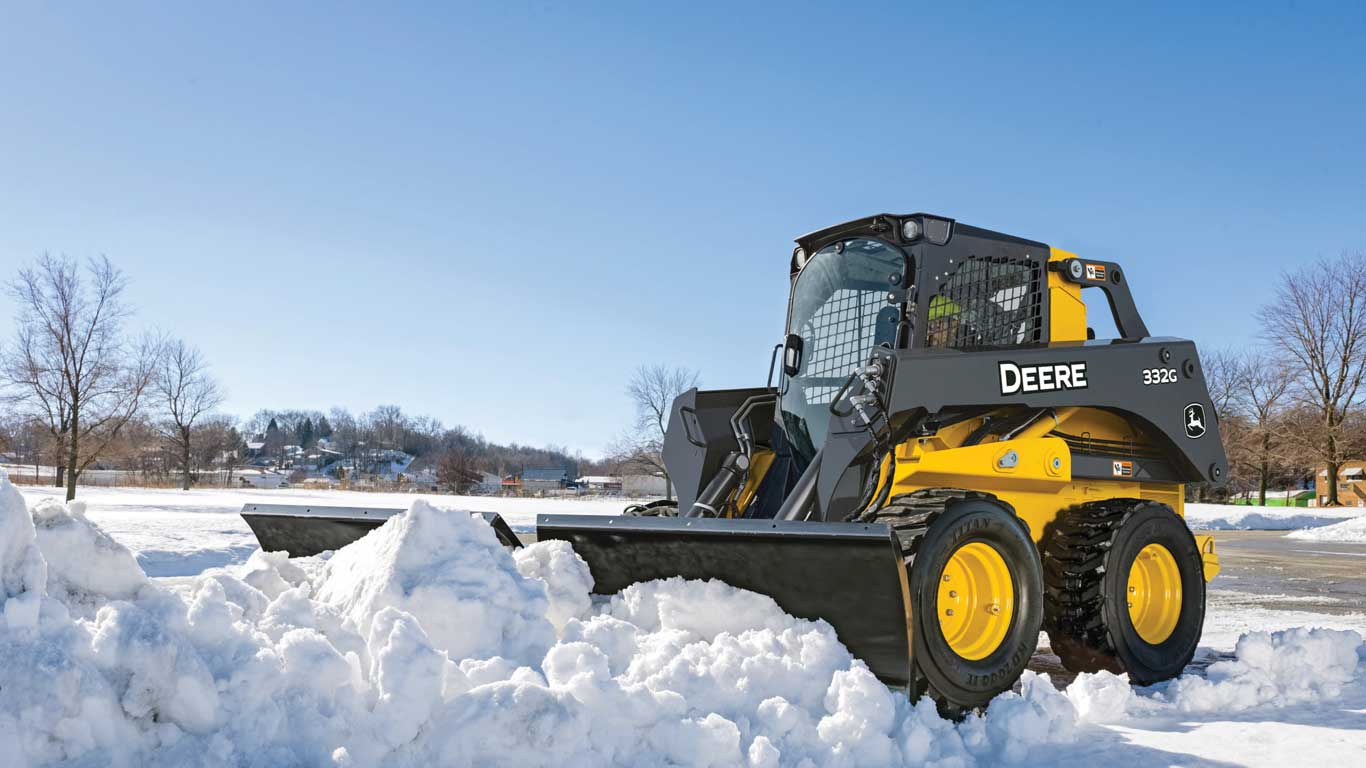 John Deere 332G skid steer with snow blade attachment clears snow