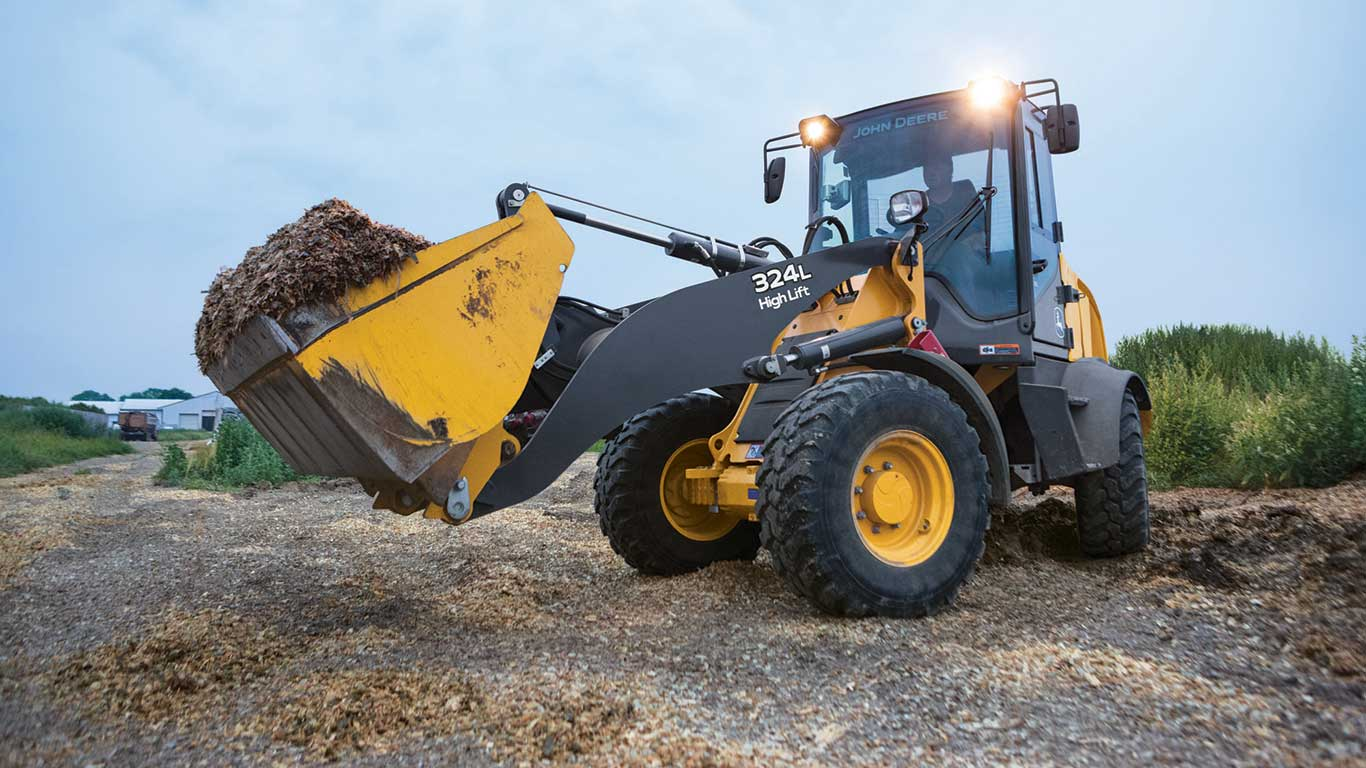 324L mini loader moving debris at dusk with headlights on