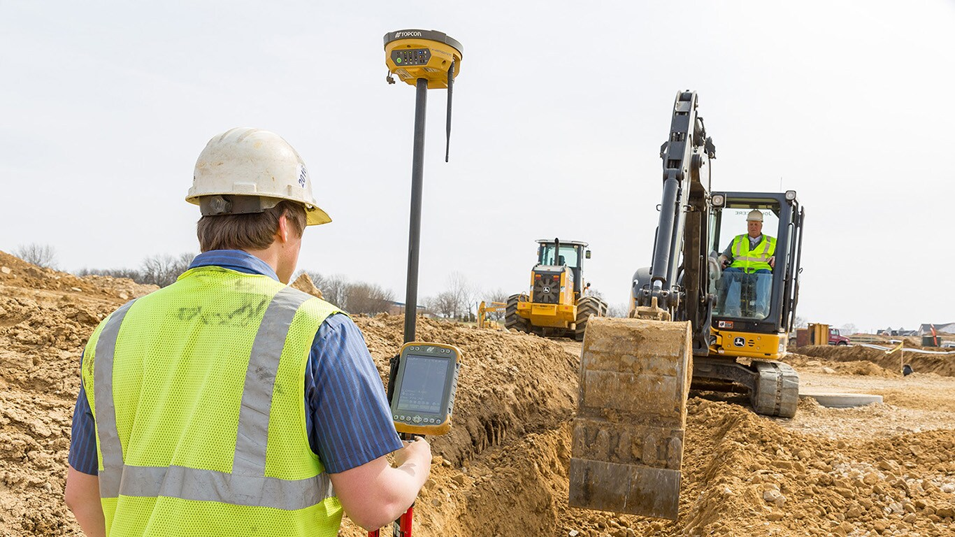 A worker holds a Topcon measuring device in a trench while an excavator digs out the trench further