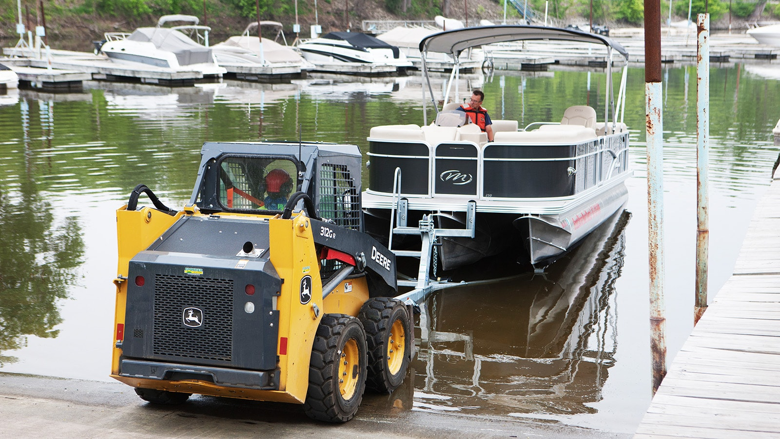 312GR Skid Steer pulls a pontoon boat out of the water