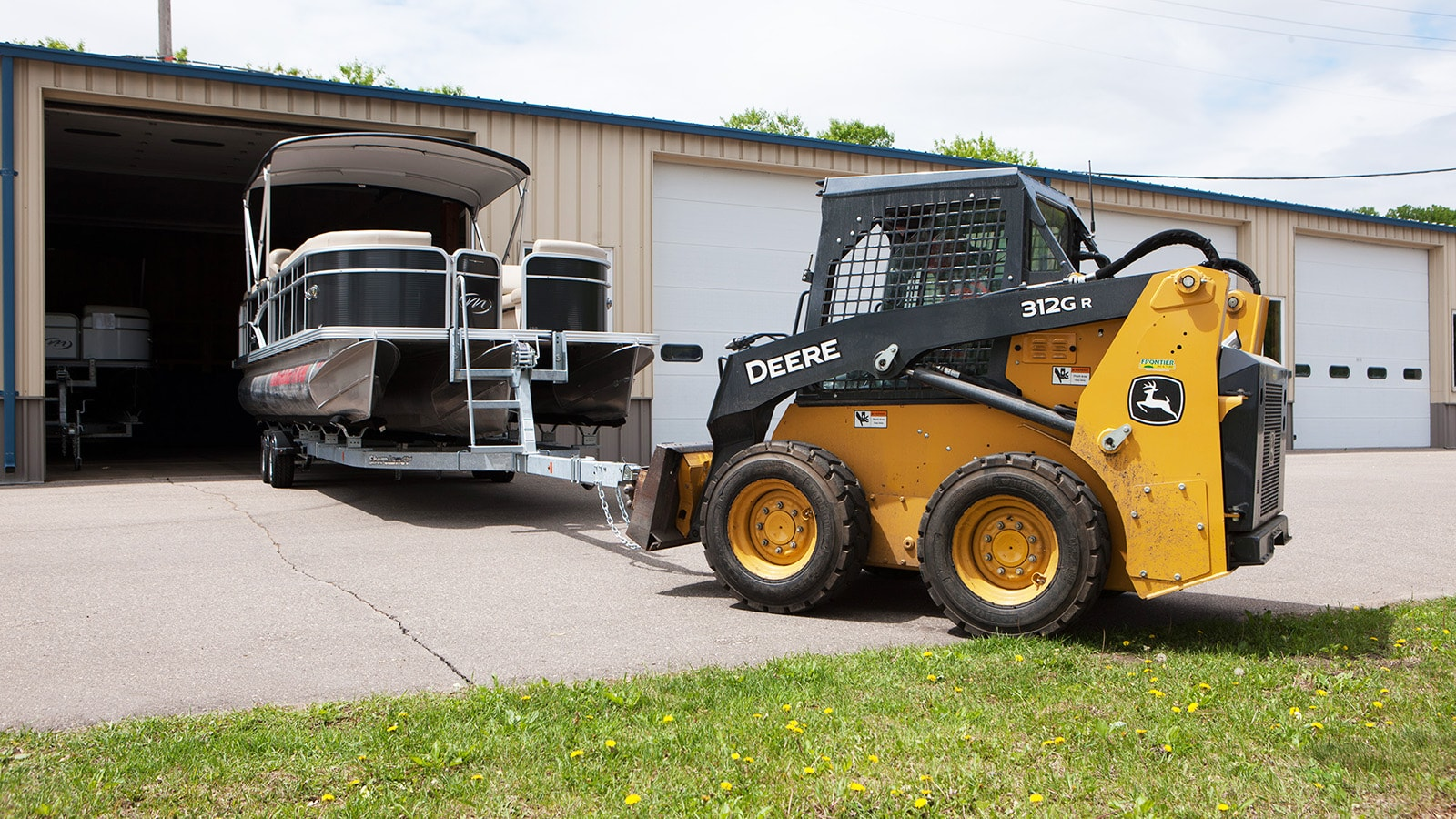 312GR skid steer pushes a pontoon boat into storage unit