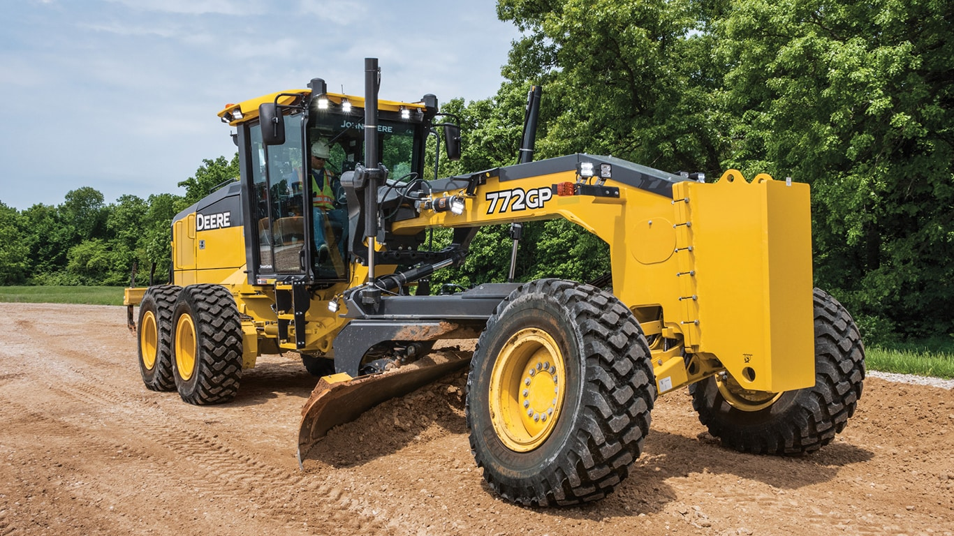 772GP SmartGrade Motor Grader grades an area of dirt, surrounded by grass and trees.