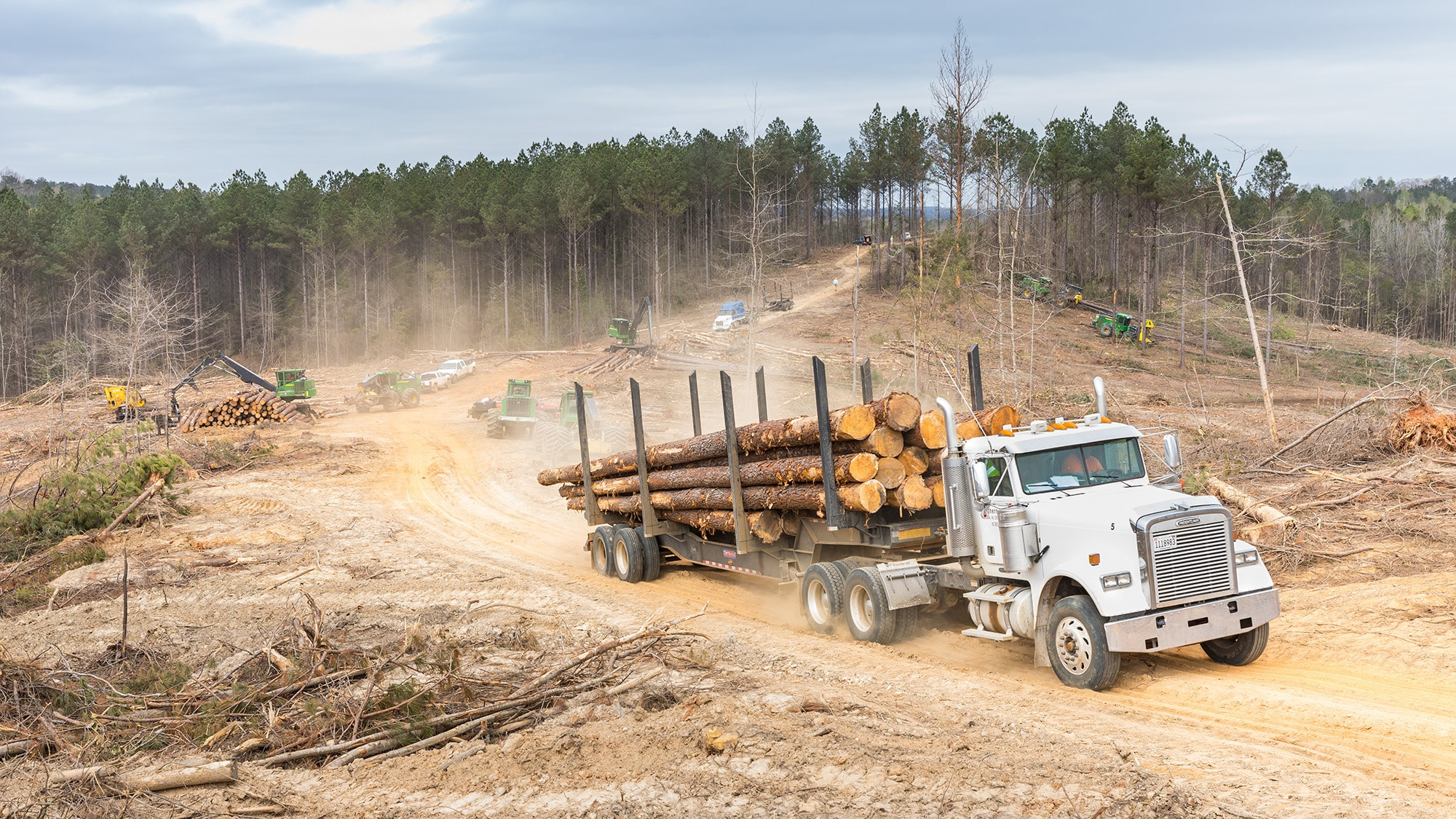 truck hauling a load of logs away from the wooded jobsite
