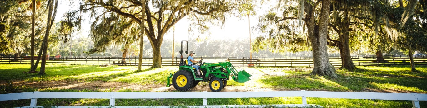 woman on tractor driving along white fencing