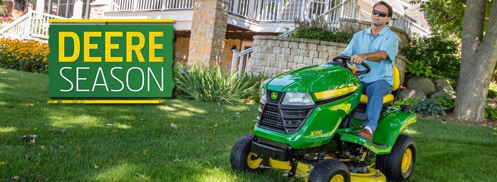 x330 John Deere lawn tractor cutting grass in yard near bushes