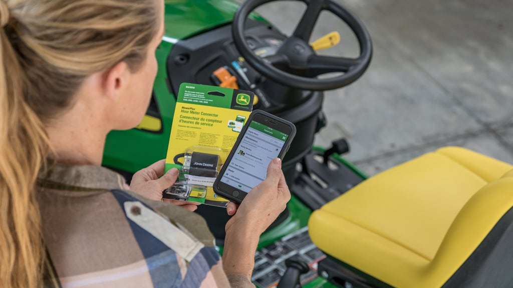 Woman standing beside a lawn mower holding an hour meter connector and her cell phone