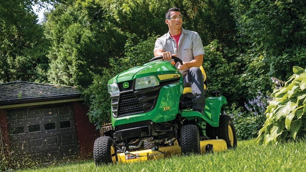 Man mowing grass with an X330 lawn tractor