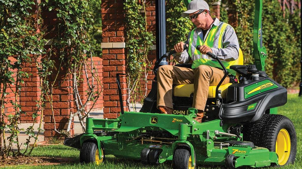 Man mowing grass beside brick columns with a Z930R ZTrak zero-turn mower.