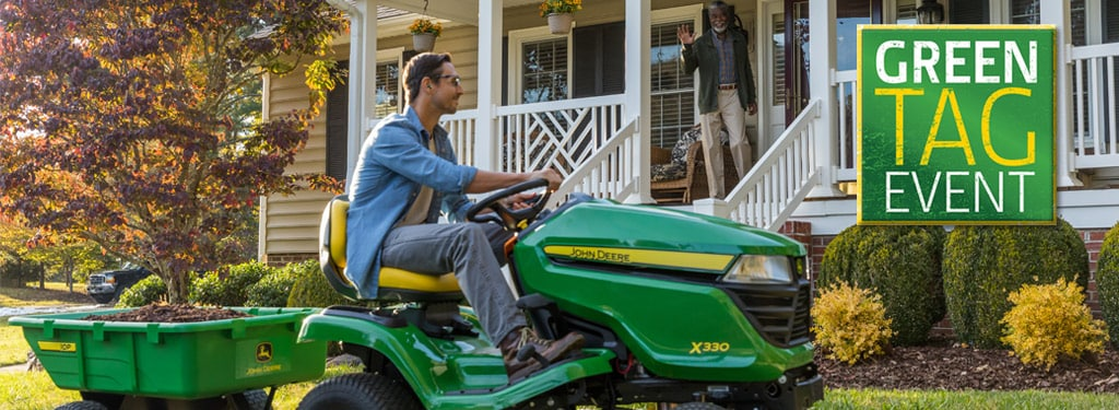 x330 John Deere lawn tractor with a cart riding by front of house