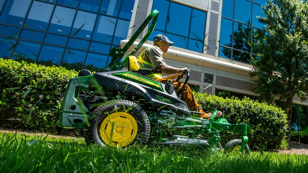 man on z915e zero turn mower mowing grass by office building