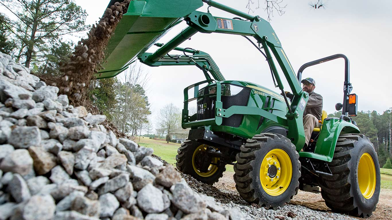 3e tractor using front loader to dump large pile of rocks