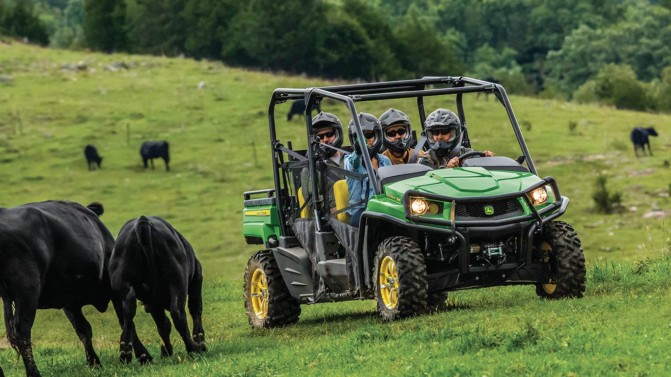 XUV560e with 4 passengers in a field with cows