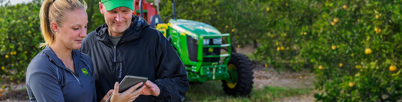 Woman and a man looking at a tablet while standing in front of a John Deere tractor in an orchard.