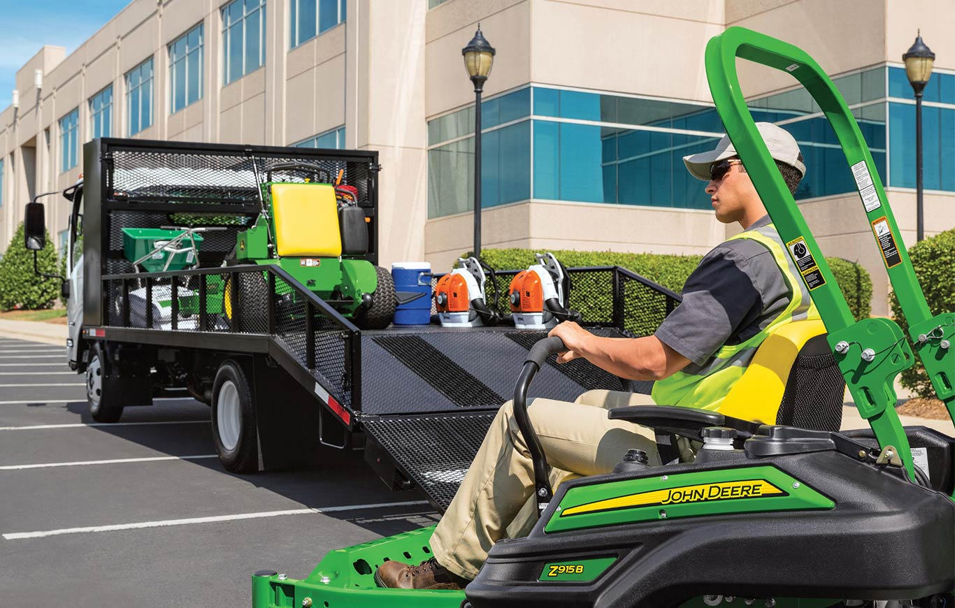 Professional landscaper unloading riding mower from trailer