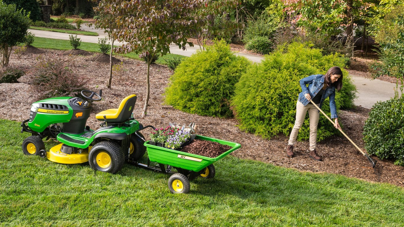 image of woman working in garden next to lawn tractor