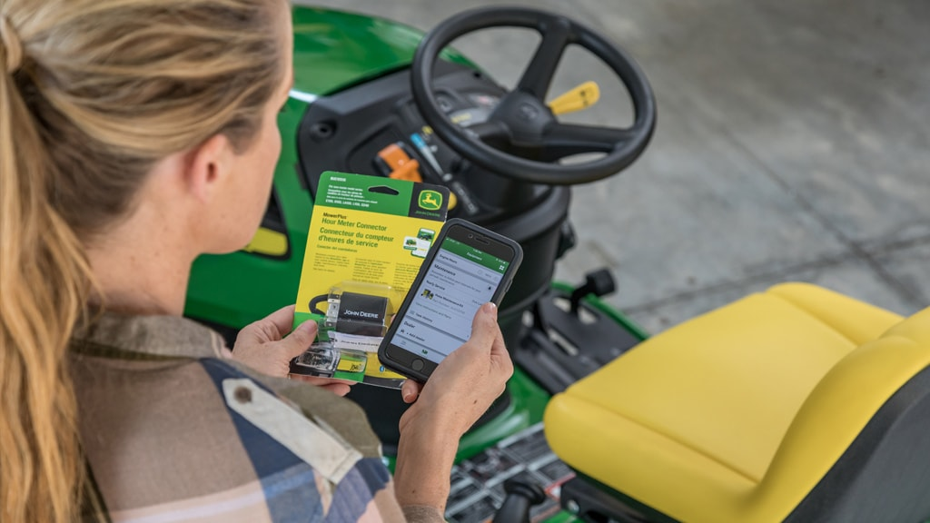 close up image of a woman holding a riding mower part and ordering on her cell phone