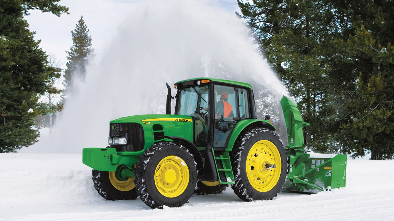 tractor with snow blower attached in the snow