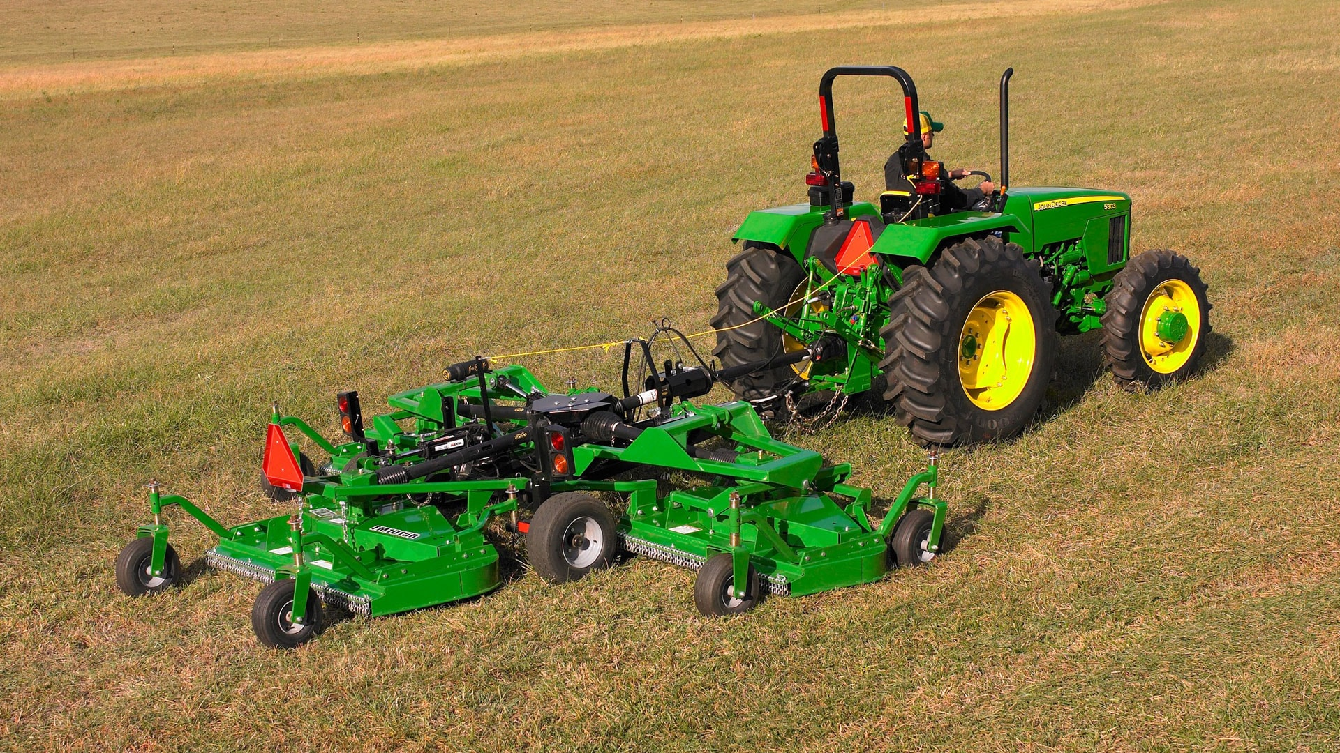 grooming mower attached to tractor in a field