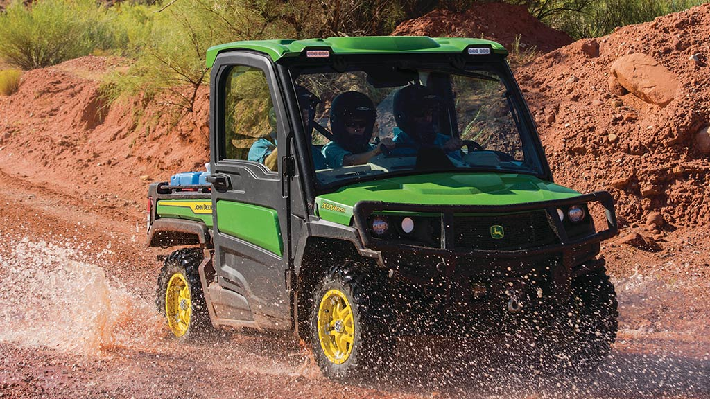 full-size gator™ driving through muddy/watery trail