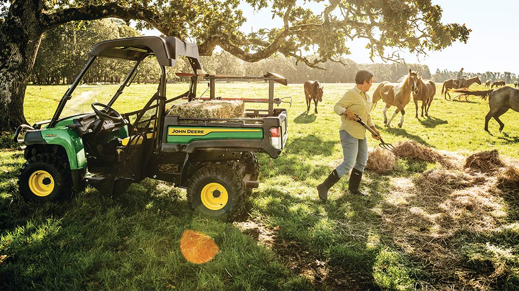 woman shoveling hay into a work series Gator™ in a field