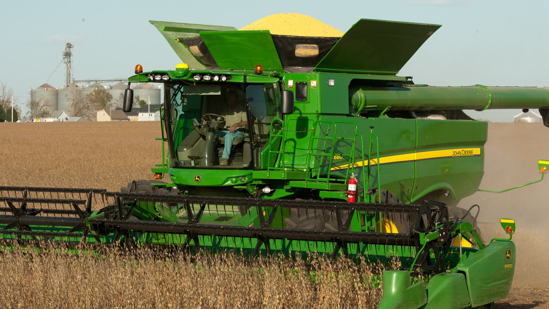 Combine with 400-Bushel Grain Tank moving through crops