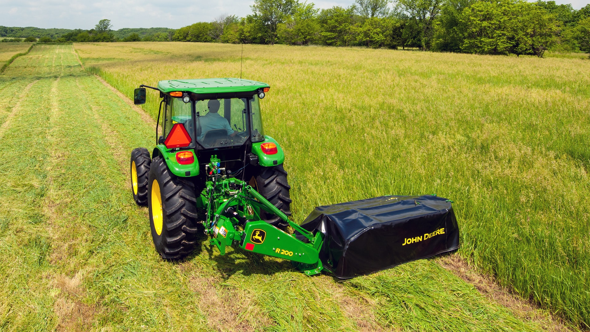 A disc mower moving through field