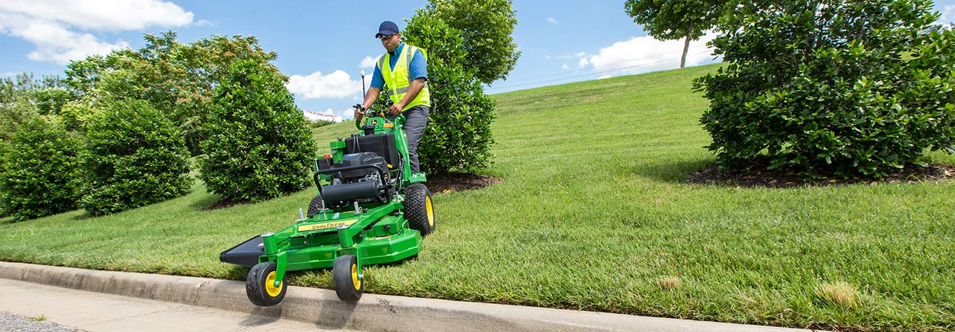man going over curb with walk behind mower
