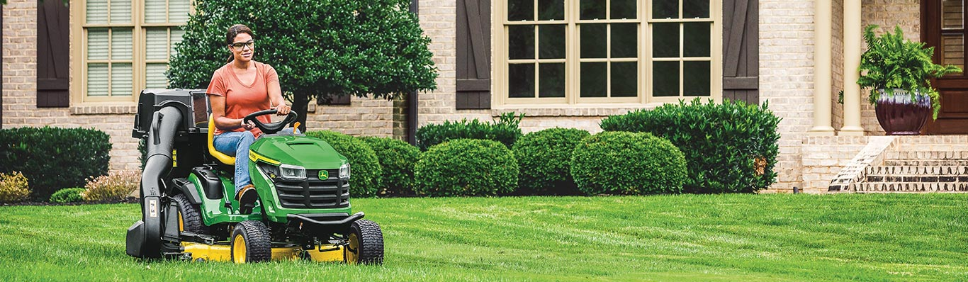 woman driving 100 series lawn tractor in yard