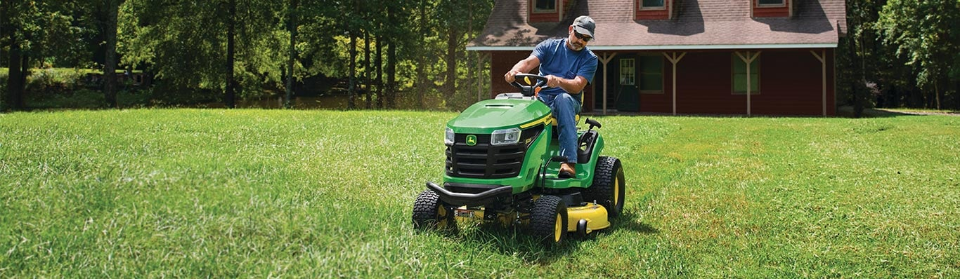 man driving 200 series lawn tractor in yard