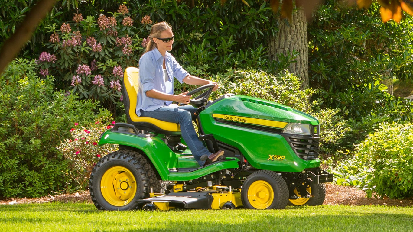 woman on x590 lawn tractor in yard