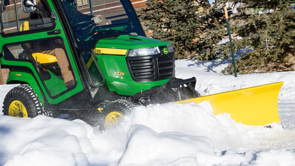 image of snow plow attachment on lawn mower plowing snow