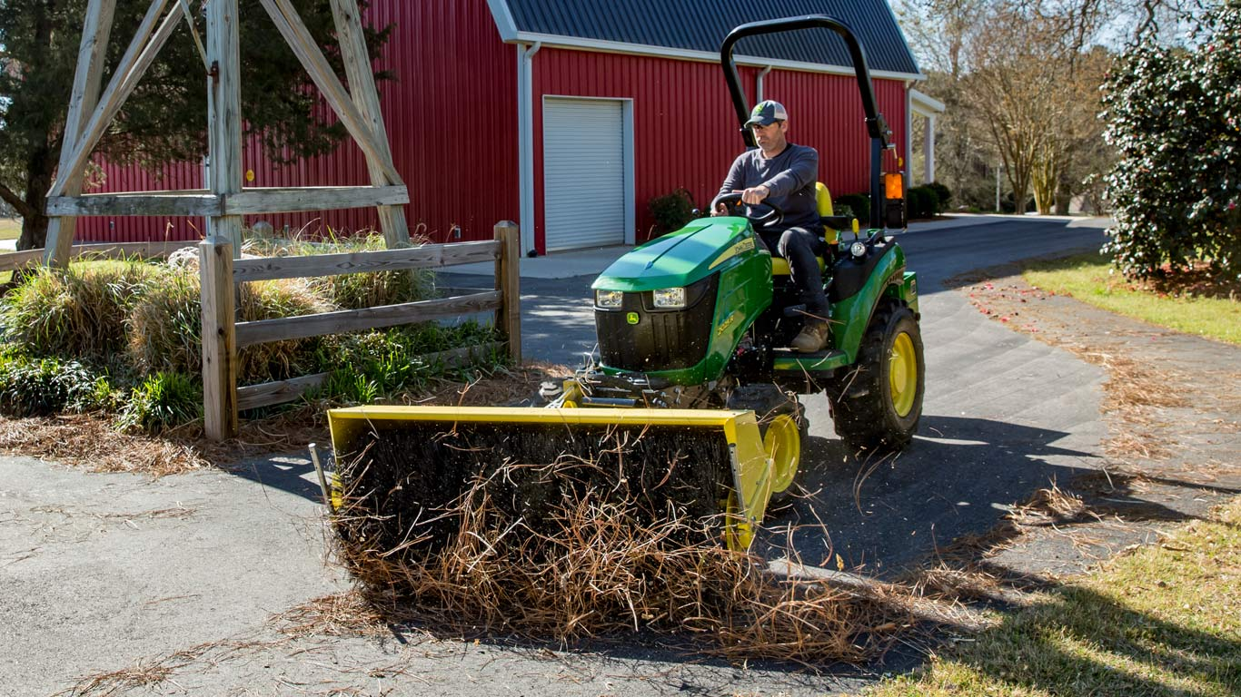 Image of the new John Deere 2025R Compact Utility Tractor moving straw near a barn
