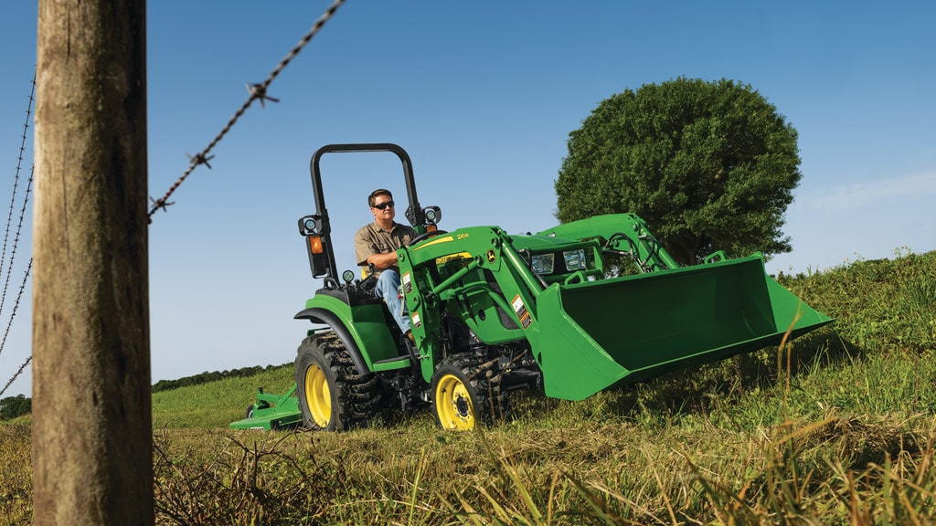 2r series tractor with a loader and mower attached driving by wire fence