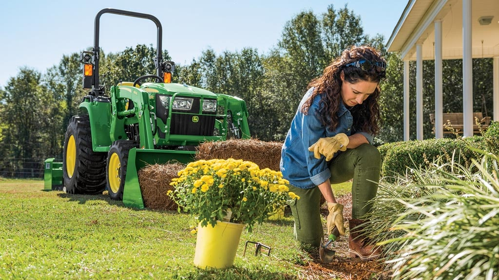 woman working in a flower bed with 3 series tractor in the background