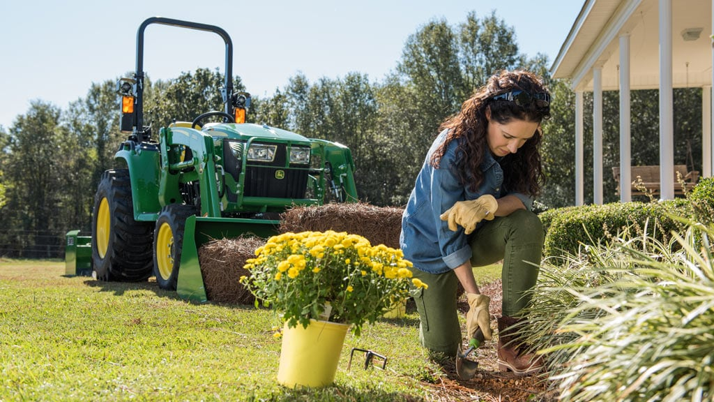 Woman working on flower bed with a 3e tractor in the background
