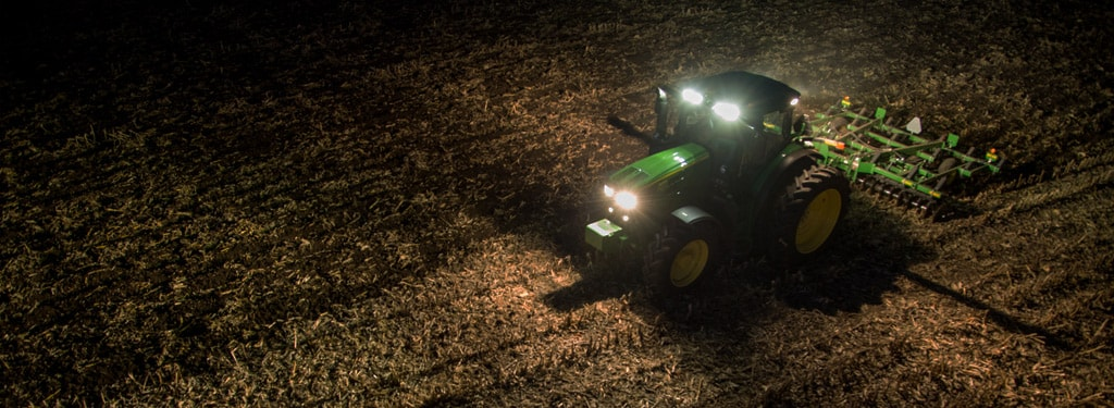 Image of row crop tractor in dark farm field with lights on