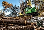 John Deere Feller Buncher with FR22B Felling Head working in the background with a pile of logs in the foreground