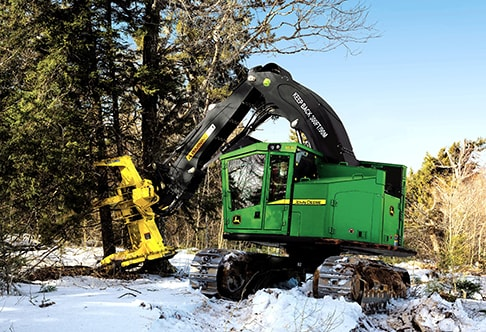 John Deere Feller Buncher with FR22B Felling Head chopping down a tree in a winter forest