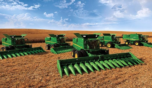 A group of five John Deere combines in a field at harvest time