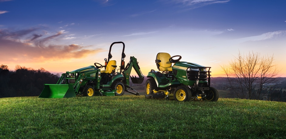 X700 Signature Series Tractor and 1 Family Sub-Compact Utility Tractor on a grassy hill at dusk