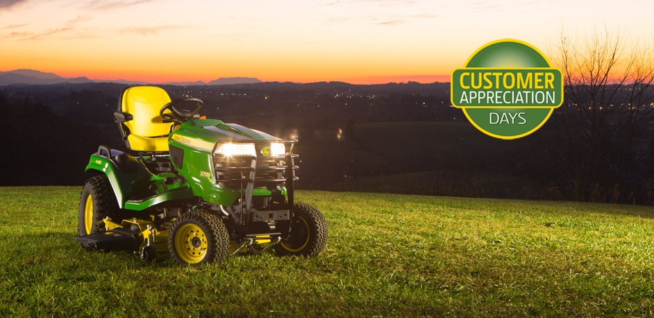 John Deere X700 Signature Series tractor with lights on sitting on a grassy hill at dusk with mountains in the background