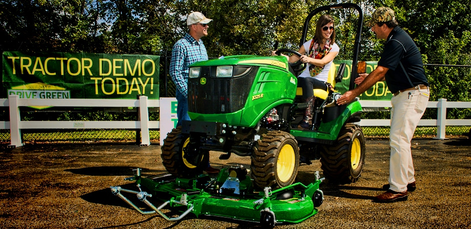 People checking out and sitting on John Deere Equipment
