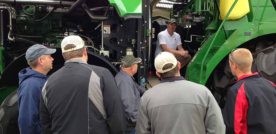 Man speaks to crowd about John Deere tractor equipment at Farm Show