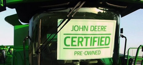 Certified Pre-Owned sign inside a John Deere combine