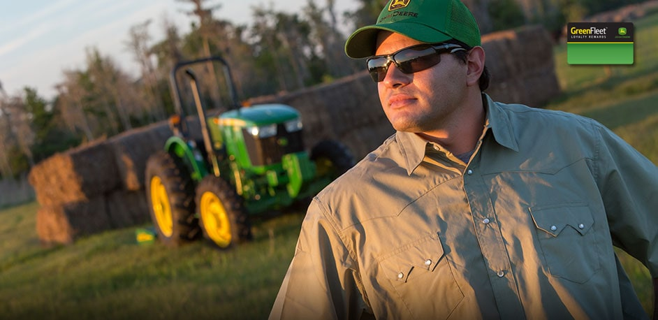 Photo of farmer with John Deere equipment in the background.