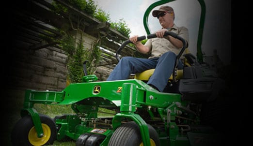 Man works using John Deere mower