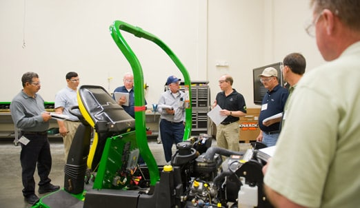 Group of people standing around a John Deere mower in a golf training class