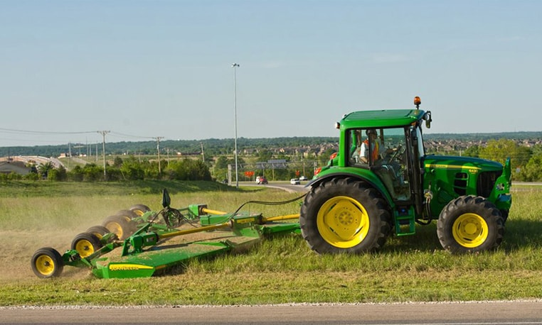 John Deere tractor with Rotary Cutter attachment cutting grass